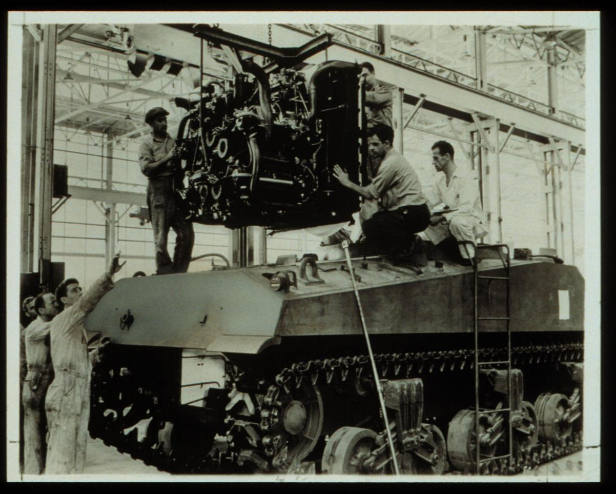 Installation of a multibank tank engine in Sherman M4A3 tanks at Chrysler Tank Arsenal, Warren, Mich., about 1942.